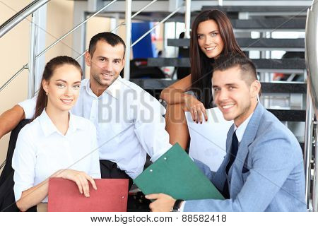 business partners sitting on stairs in office building and discussing work, computer, smiling