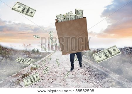 Businessman carrying bag of dollars against stony path leading to misty city horizon