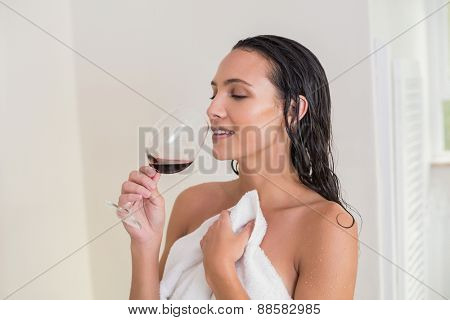 Pretty brunette drinking red wine in her bedroom