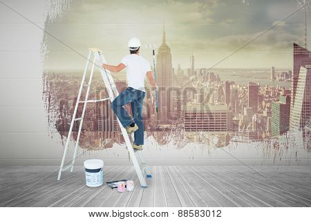 Man on ladder painting with roller against room with large window looking on city