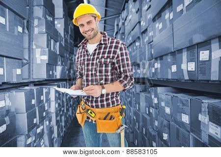 Confident male repairman writing on clipboard against shelves with boxes in warehouse