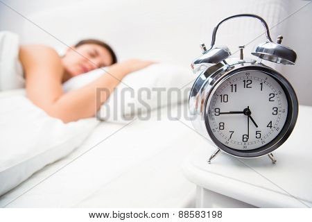 Pretty brunette sleeping in bed with alarm clock at home in the bedroom