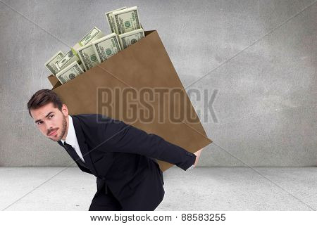 Businessman carrying something with his back and hands against grey room