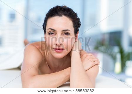 Smiling brunette relaxing on massage table in a healthy spa