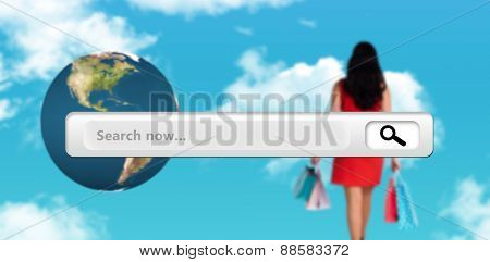 Woman standing with shopping bags against blue sky