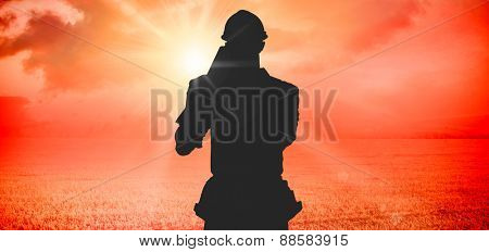Happy carpenter carrying wooden planks against sunrise over field