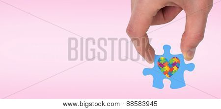 Hand holding jigsaw piece against pink