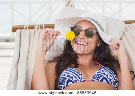 Pretty brunette relaxing on a hammock and eating a lollipop in patio
