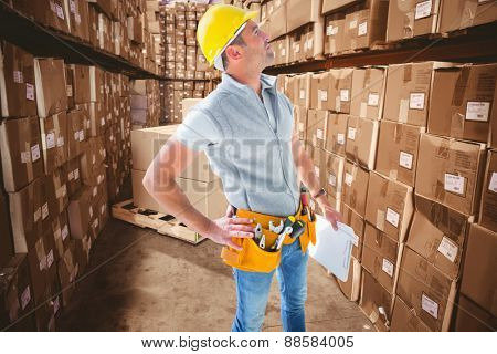 Carpenter looking up against boxes in warehouse