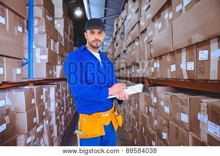 Handyman in blue overall writing on clipboard against shelves with boxes in warehouse