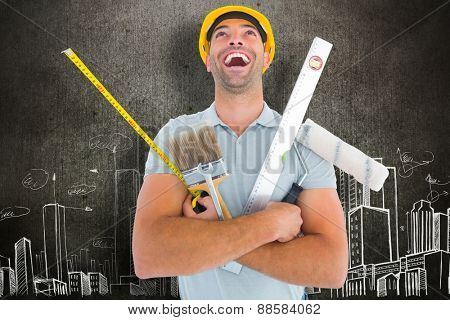 Laughing manual worker holding various tools against hand drawn city plan
