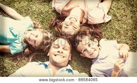 Happy family lying on the grass in a circle smiling at camera in park