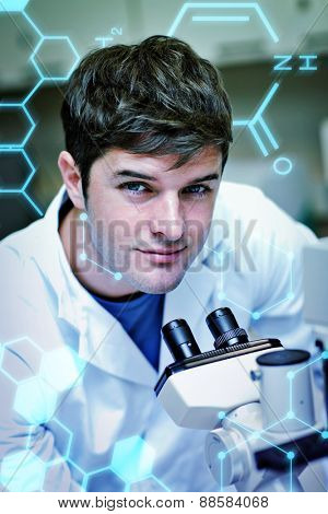 Science and medical graphic against handsome male scientist using a microscope