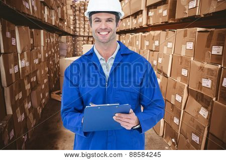 Confident supervisor writing notes against boxes in warehouse