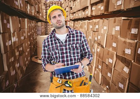 Thoughtful male repairman writing on clipboard against boxes in warehouse