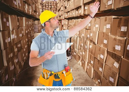 Male supervisor with hand raised holding clipboard against boxes in warehouse