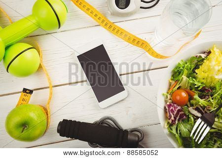 Smartphone with indicators of healthy lifestyle on wooden table