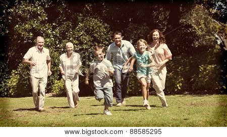 Happy multi generation family running towards camera in the park on sunny day