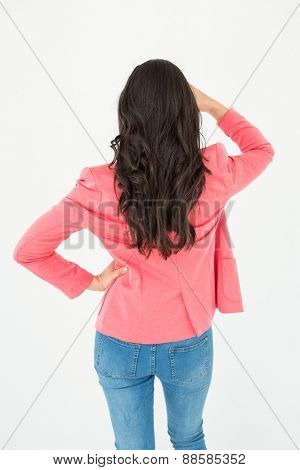 Elegant brunette standing back to camera and looking away on white background