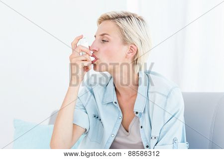 Pretty blonde woman using her inhaler in the living room