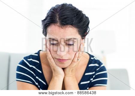 Unhappy woman sitting on the couch on white background