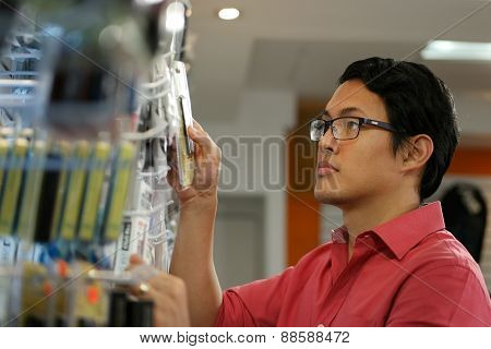 Chinese Man Ordering Usb Drive On Shelf In Computer Shop