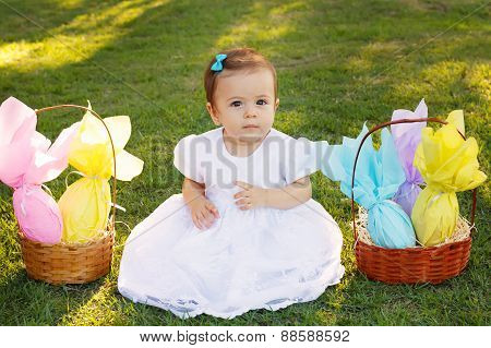 Cute Little Baby Girl With Wicker Basket With Chocolate Eggs