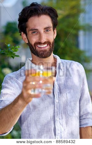 portrait of young man standing outdoors in garden with cocktail drink