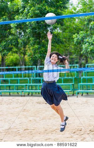 Cute Thai Schoolgirl Is Playing Beach Volleyball In School Uniform. Focus On The Model Face.