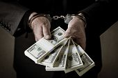 stock photo of handcuffs  - Man in suit arrested with handcuffs and money in his hands - JPG