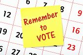 image of voting  - Remember To Vote reminder on a yellow sticky note attached to a wall calendar - JPG