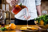 foto of sangria  - Man pours homemade sangria with fruit pieces in a glass - JPG