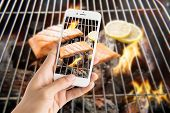 pic of grill  - Taking photo of grilled salmon with lemon on the flaming grill