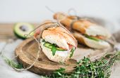 stock photo of baguette  - Salmon and avocado sandwiches with fresh thyme in baguette tied up with a decoration rope on a rustic wooden board over rough wood background - JPG