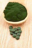 stock photo of green algae  - Closeup of an organic spirulina algae powder and pills in a wooden spoon - JPG