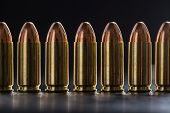 foto of pistols  - Number pistol cartridge 9 mm caliber on a black background - JPG
