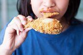 foto of fried chicken  - A girl with opening mouth about to eat deep fried chicken legs or drumsticks - JPG