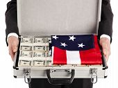 stock photo of american money  - Businessman with briefcase full of money and american flag - JPG