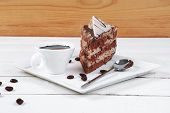 picture of cream cake  - breakfast hot coffee mug and cream chocolate layer cake decorated with white chocolate slice and cream flower on white plate over wood - JPG