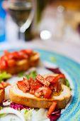 foto of antipasto  - Fresh homemade crispy Italian antipasto bruschetta topped with tomato - JPG