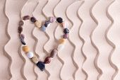 pic of agate  - Decorative pebble heart of waterworn alluvial quartzite agate and basalt stones symbolic of love and romance on golden beach sand with an ornamental pattern of wavy lines and copyspace - JPG