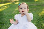 stock photo of teething baby  - Cute happy smiling little baby girl in white dress scratching first teeth in park on green grass - JPG