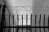stock photo of barbed wire fence  - An inner city fence with sharpened vertical bars - JPG