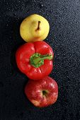 stock photo of yellow-pepper  - macro yellow pear red apple and red bell peppers on black background studio - JPG