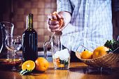 picture of sangria  - The man squeezes grapefruit juice in a decanter for making home sangria for home party - JPG