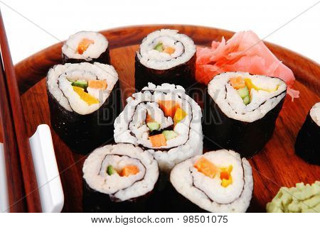 Japanese Traditional Cuisine - California Roll with Salmon (sake), Cream Cheese and Tuna (maguro) . on wooden plate with wasabi and ginger isolated over white background
