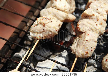 raw chicken breast shish kebab meat coated with sauce of dijon mustard prepared on grill over charcoal