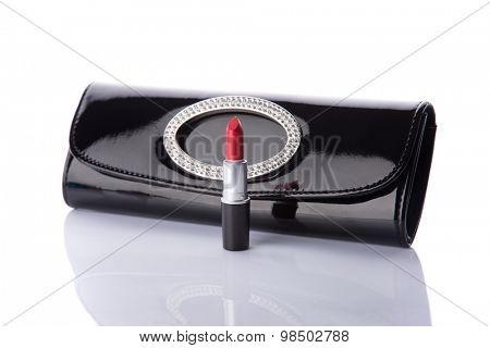 Black handbag clutch and classic red lipstick, isolated on white background with reflection