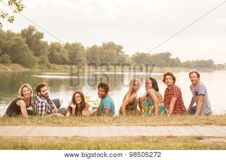 8 young good looking adults laying on grass close to lake in summerly feel
