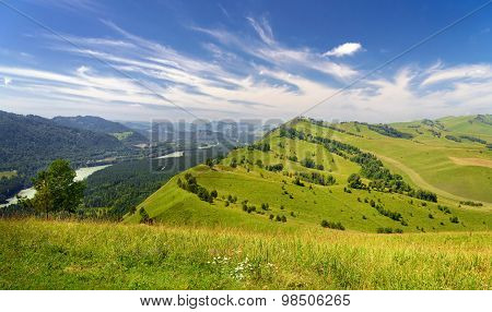 Beautiful Summer Landscape: Mountains Covered By Trees, Green Hills And Blue Sky With White Clouds (